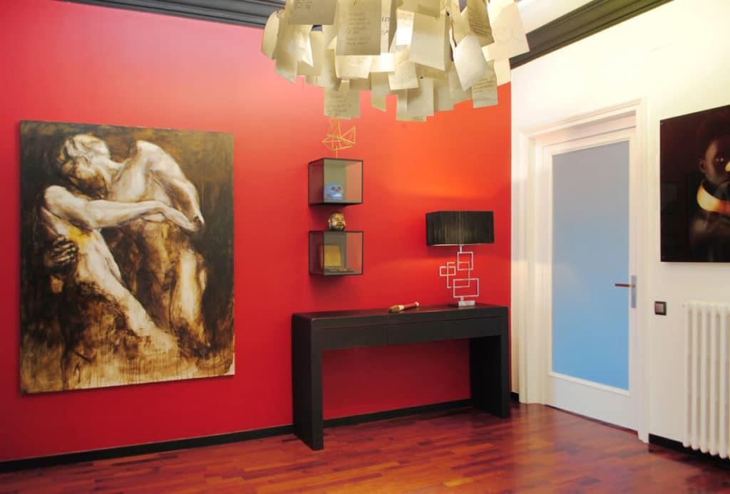 Reforma de interiorismo de un piso en Barcelona diseñado por el estudio de diseño internacional Manuel Torres Design donde se ve la entrada decorada en tonos rojos