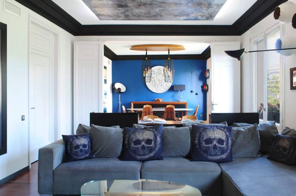 Reforma de interiorismo de un piso en Barcelona diseñado por el estudio de diseño internacional Manuel Torres Design donde se ve un comedor decorado en tonos azules y blanco con mesa de madera y sofó decorado de azul