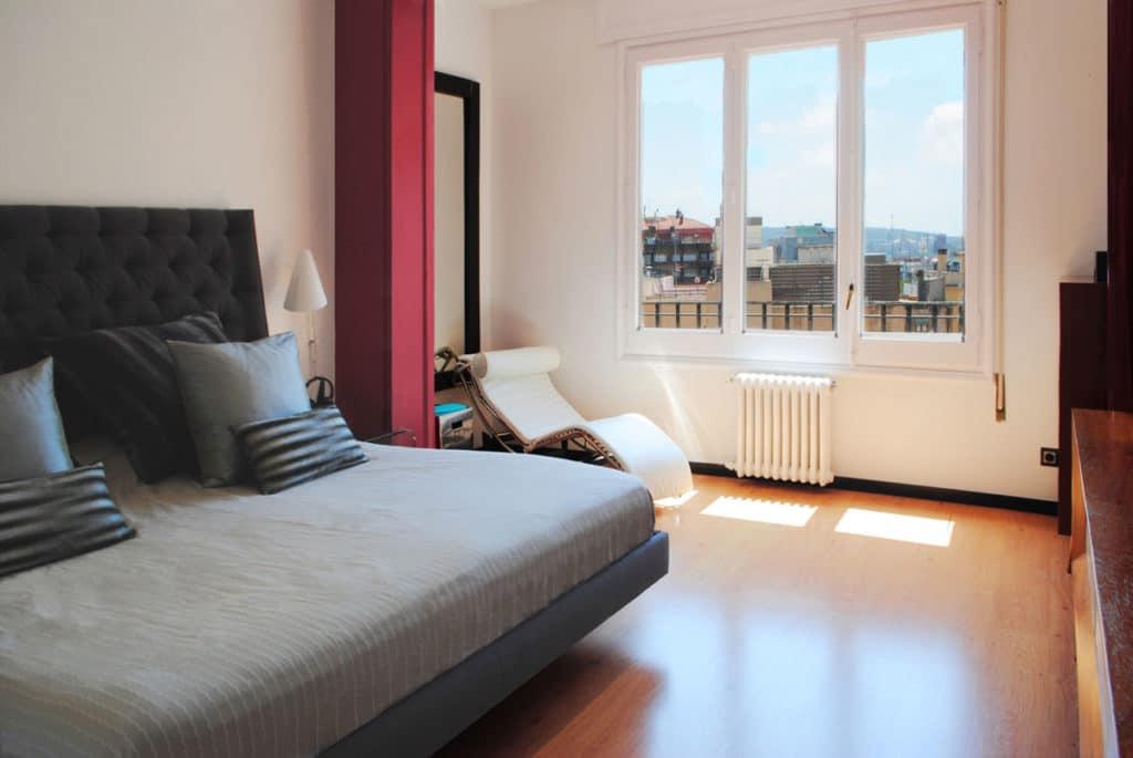 Reforma de interiorismo de un piso en Barcelona diseñado por el estudio de diseño internacional Manuel Torres Design donde se ve la habitación de matrimonio decorada en tonos claros y detalle rojo