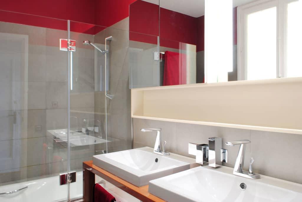 Reforma de interiorismo de un piso en Barcelona diseñado por el estudio de diseño internacional Manuel Torres Design donde se ve el baño decorado en tonos blancos y rojos