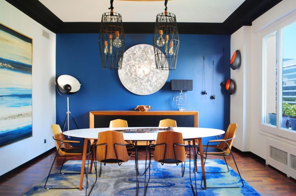 Reforma de interiorismo de un piso en Barcelona diseñado por el estudio de diseño internacional Manuel Torres Design donde se ve un comedor decorado en tonos azules y blanco con mesa de madera