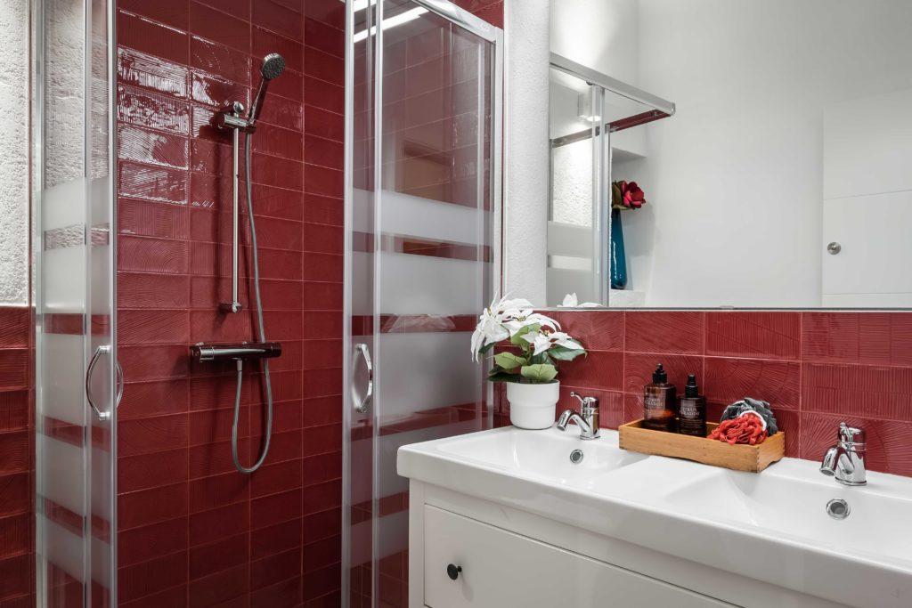 Baño en color rojo y blanco resultado final de la reforma integral y el diseño de interiores de esta vivienda en Barcelona por parte del estudio de diseño internacional Manuel Torres Design